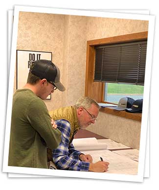mike and luke carey looking over blueprints
